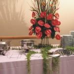 Mesa de banquete com toalha e rechauds, pratos, garfos e facas de mesa